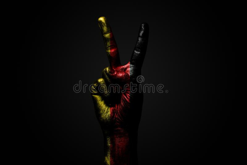 A hand with a drawn Germany flag shows an PEACE sign, a symbol of peace, friendship, greetings and peacefulness on a dark. Background. Horizontal frame stock photos