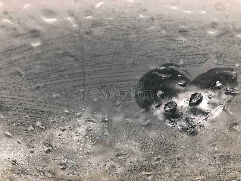 Hand drawn heart shape on a window pane with rain drops stock images