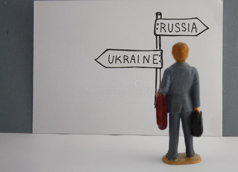 Hand-drawn road sign Russia or Ukraine direction.  Miniature man making decision, chooses between russia and ukraine royalty free stock image