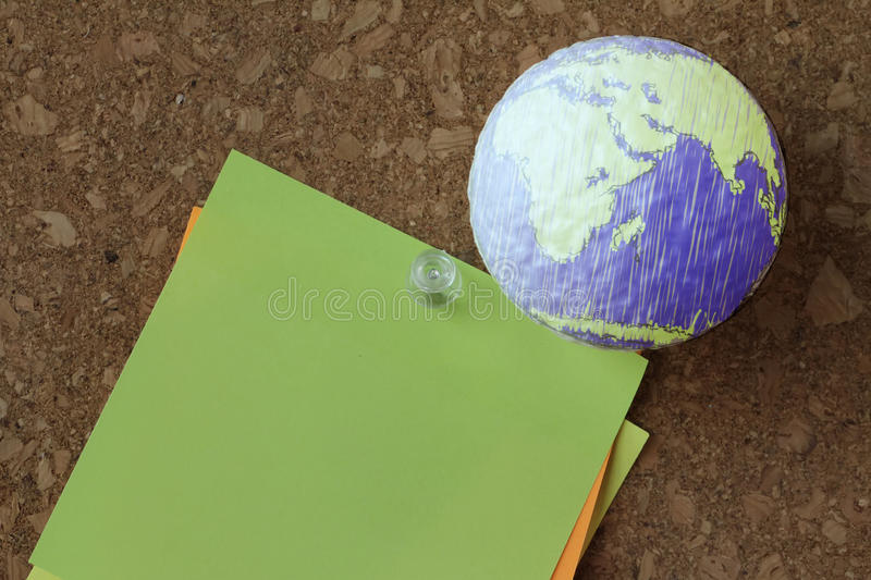 Hand drawn texture globe with pin and business graph. On sticky note on cork board as concept stock photo