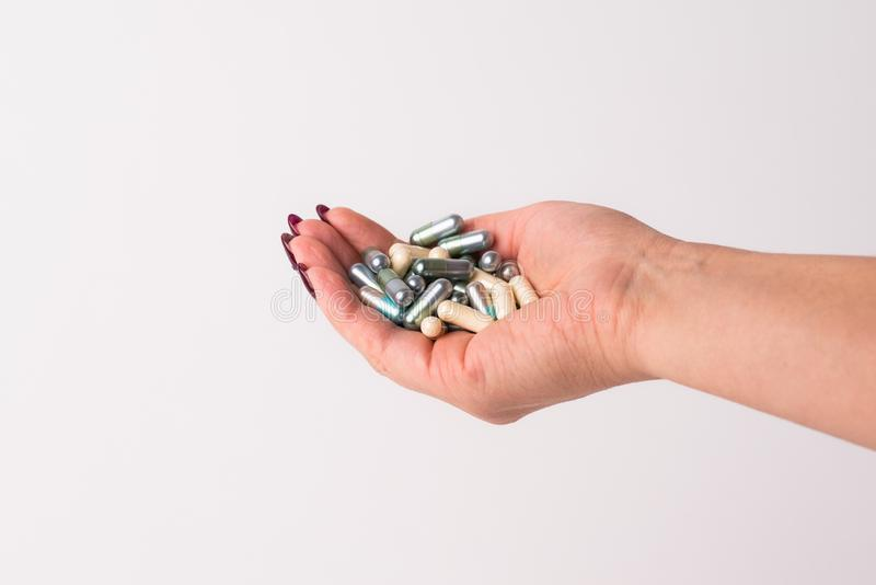 Close-up of a hand holding various capsules and medicines. White isolated background. stock photo