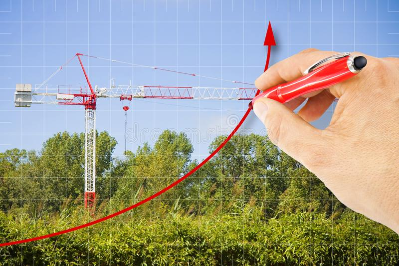 Hand draws a growing chart about building activity against a background with a tower crane in a construction site surrounded by. Nature - concept image stock photo