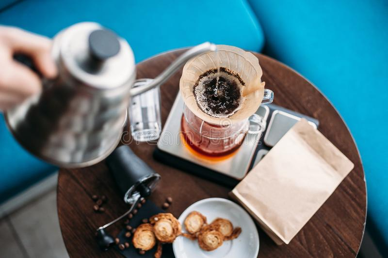 Hand drip coffee, barista pouring water on coffee ground with filter. Simple set for manual brewing royalty free stock photo