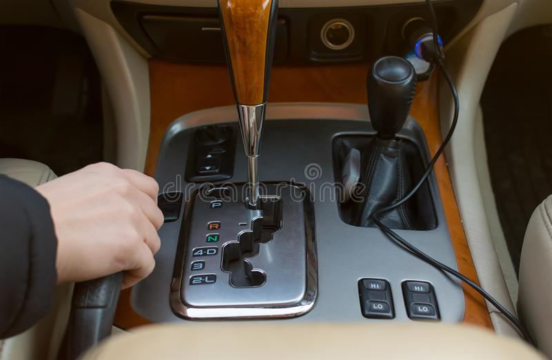 The hand of the driver of the car holding the brake lever, on the background of the automatic transmission controls. Close-up view stock photography