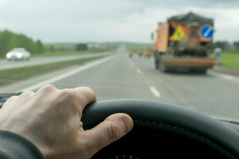 Hand driver on the steering wheel of the car. The hand of the driver who moves on a country road in cloudy weather royalty free stock photography
