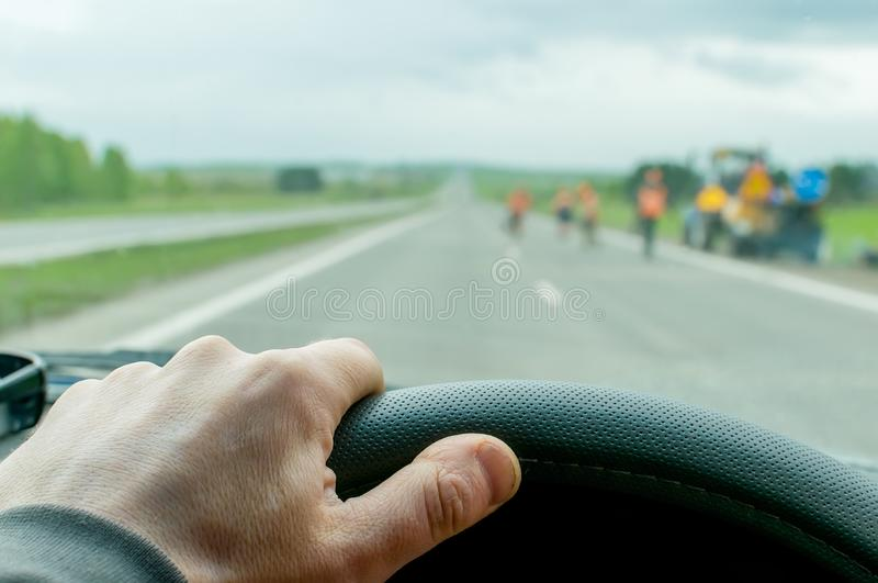 Hand driver on the steering wheel of the car. The hand of the driver who moves on a country road in cloudy weather stock photography