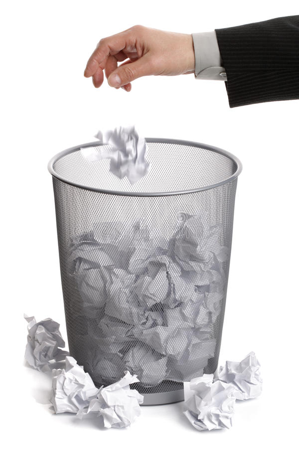 Hand dropping paper into wastepaper bin royalty free stock photography