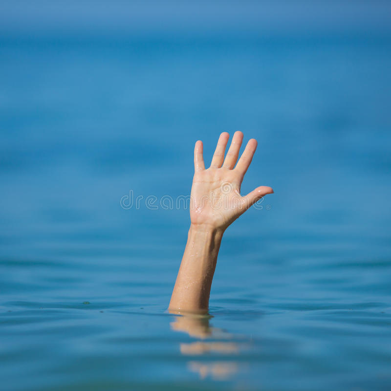 Hand of drowning man in sea or ocean asking for help stock photos