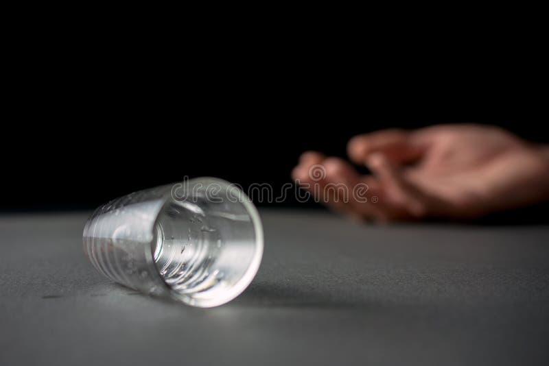 Hand druckit liggande tomt exponeringsglas av vodka eller alkoholdrycken fotografering för bildbyråer