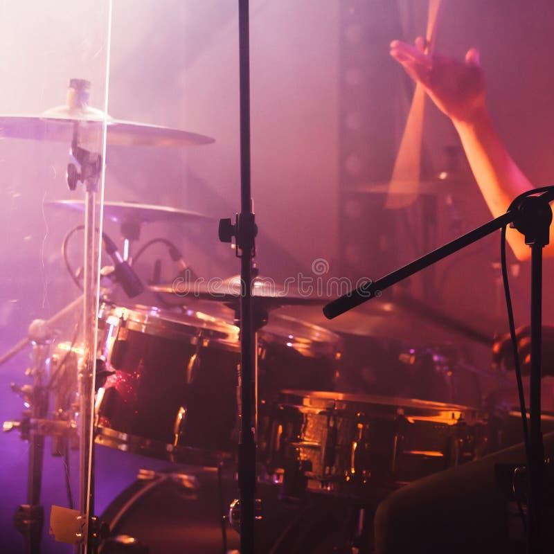 Hand with drumsticks near rock drum set. Drummer hand with drumsticks near rock drum set. Warm toned closeup photo, soft selective focus stock images
