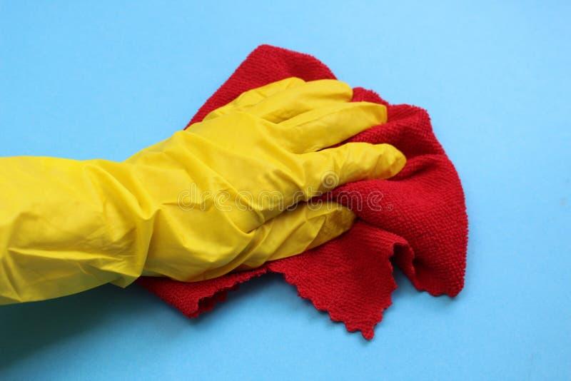 Hand in einem gelben Gummihandschuh, der einen roten Lappen hält lizenzfreie stockfotos