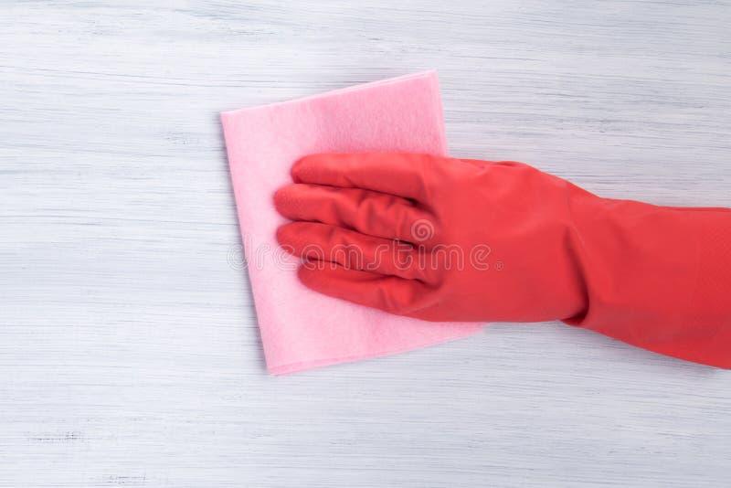 Hand in einem roten Handschuh wischt die Oberfläche eines rosa Lappens, Nahaufnahme, auf einem hellen Hintergrund ab lizenzfreie stockbilder