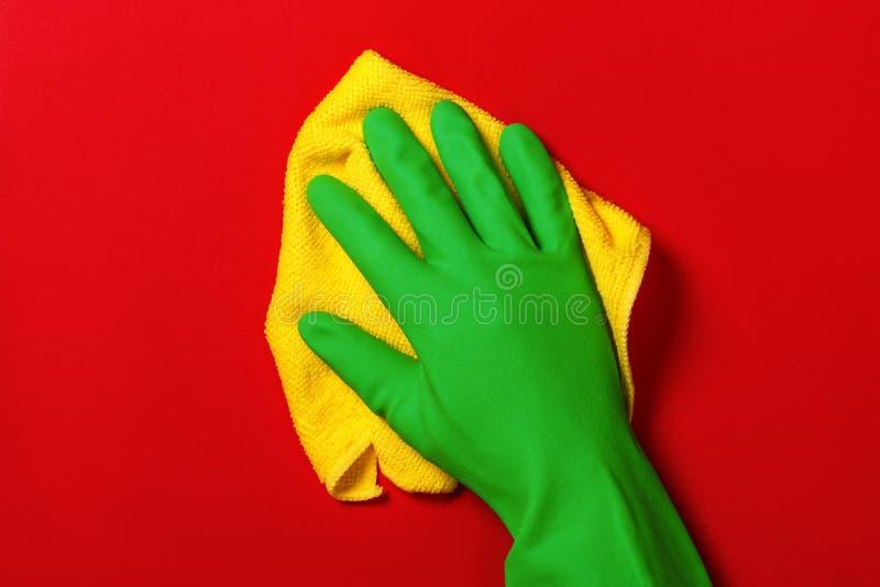 Hand in einen grünen Schutzhandschuh mit einer gelben Serviette auf einem roten Hintergrund Das Konzept der Reinigung, der häusli lizenzfreie stockfotos