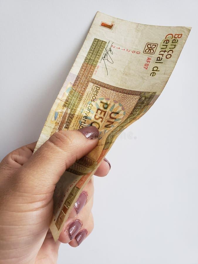 Hand einer Frau, die eine kubanische Banknote von einem Pesokabriolett hält lizenzfreie stockbilder