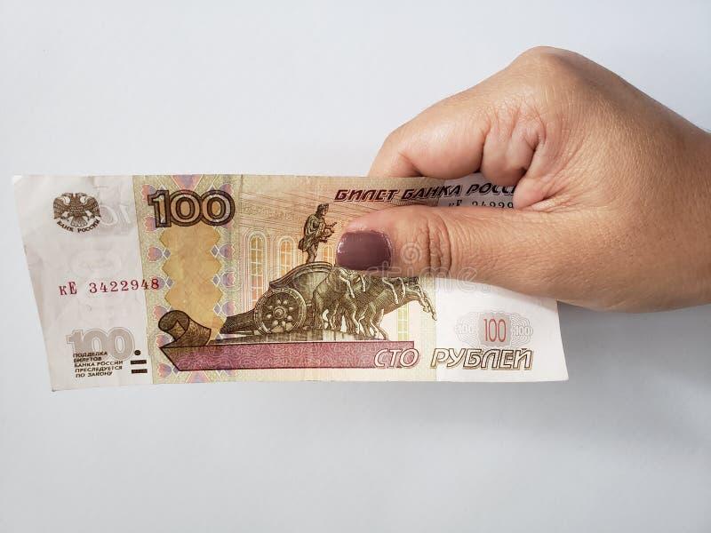Hand einer Frau, die eine russische Banknote von 100 Rubeln hält lizenzfreie stockbilder