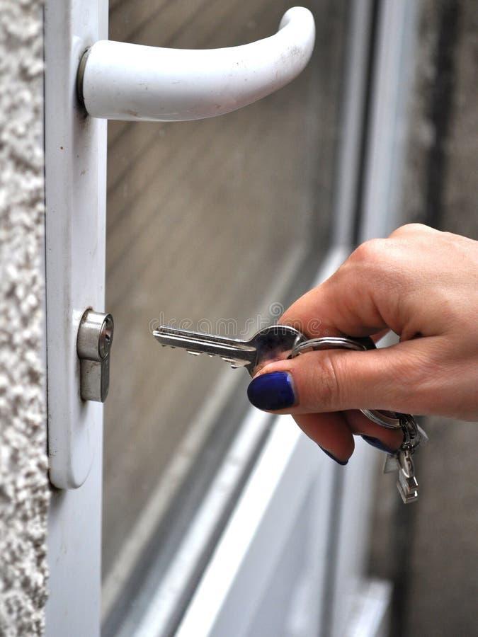 Hand einer Frau, die, eine Tür öffnend schließt lizenzfreies stockbild
