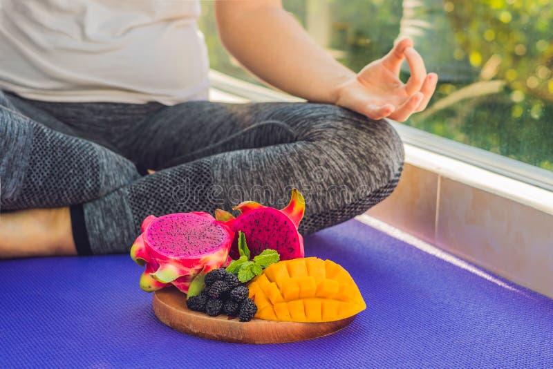 Hand einer Frau, die in einer Yogahaltung, sitzend im Lotos mit Früchten vor ihrer Drachefrucht, -mango und -maulbeere meditiert lizenzfreies stockbild