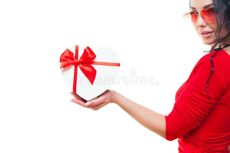 Hand einer Frau und mit rotem Herz-förmigem der Geschenkbox, lokalisiert auf weißem Hintergrund Verarbeitet mit Weinleseart lizenzfreie stockfotos