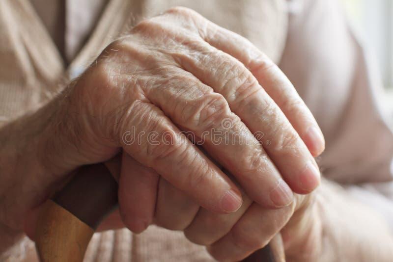 Hand eines älteren Mannes mit einem Stock stockbild