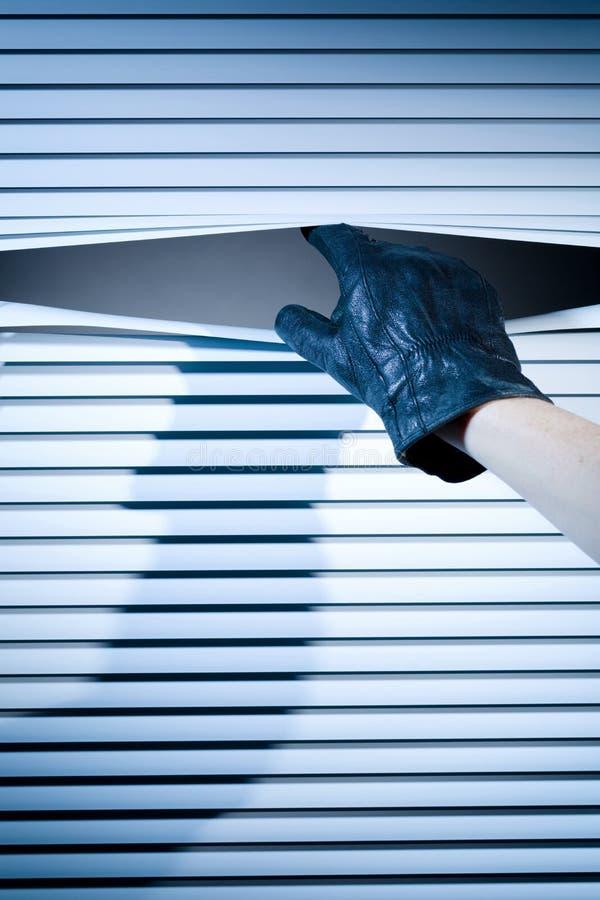 Hand eines Diebes an einem Fenster lizenzfreie stockfotografie