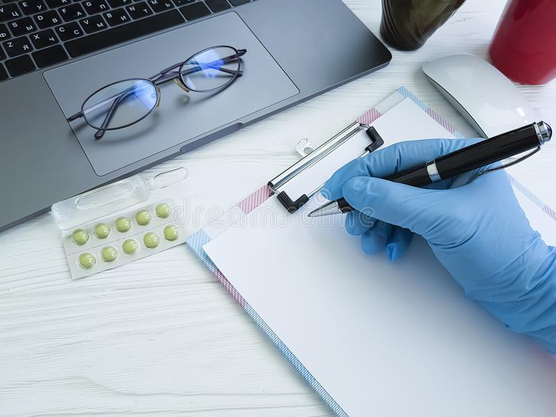 Hand eines Doktors in einem Handschuh schreibt auf den Desktop, Laptop stockbilder