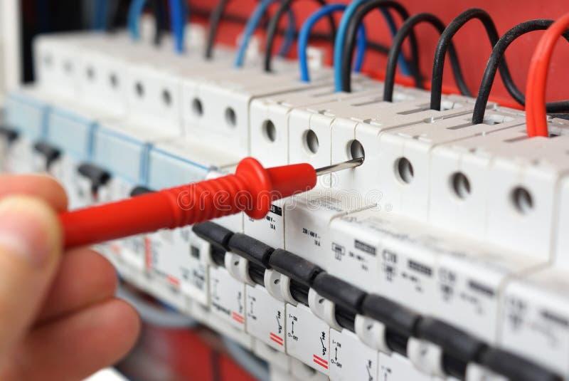 Hand eines Elektrikers mit Vielfachmessgerätsonde an einem elektrischen Schalter lizenzfreie stockfotos