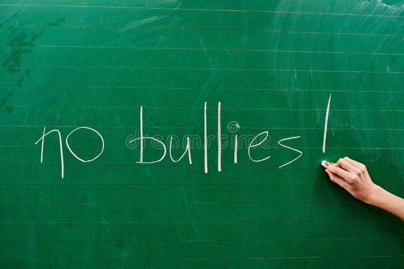 Hand eines jungen Mädchens, das den Wörtern KEINEN TYRANNE auf die grüne Schulbehörde schreibt lizenzfreie stockfotos