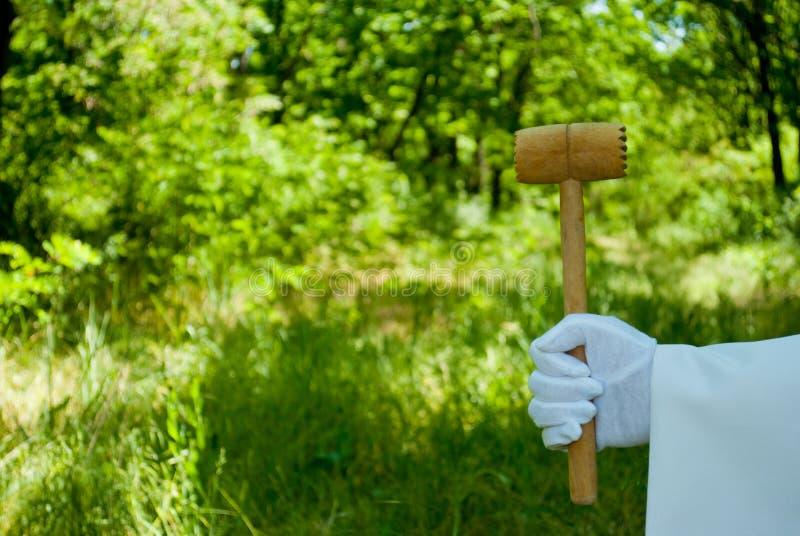 Hand eines Kellners in einem weißen Handschuh hält einen hölzernen Hammer im Freien lizenzfreies stockbild