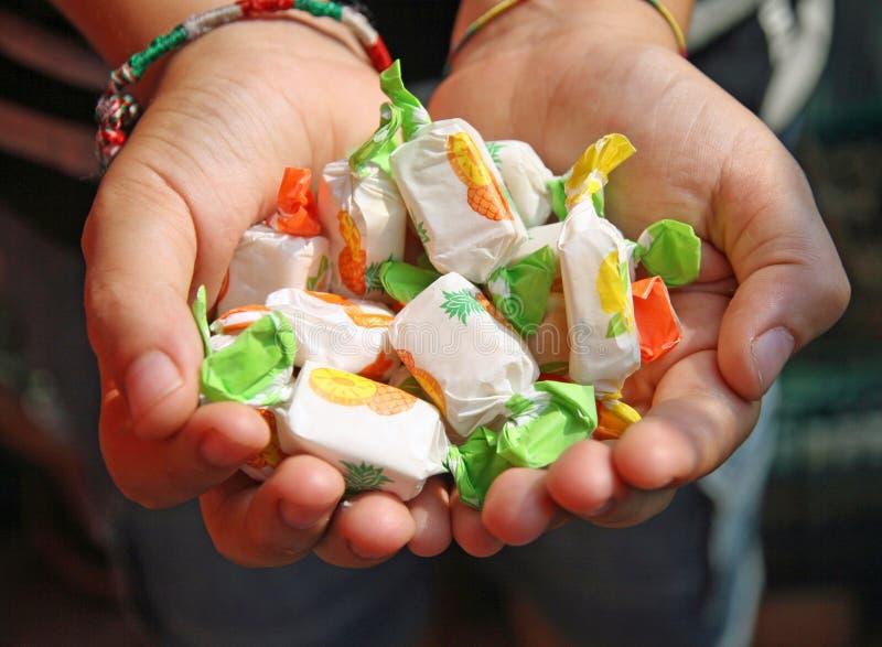 Hand eines Kindes voll der Süßigkeit lizenzfreie stockfotos