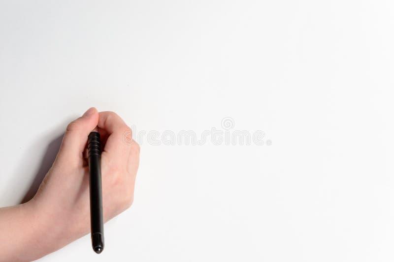 Hand eines kleinen Jungen mit einem schwarzen Stift auf einem weißen Hintergrund stockbilder