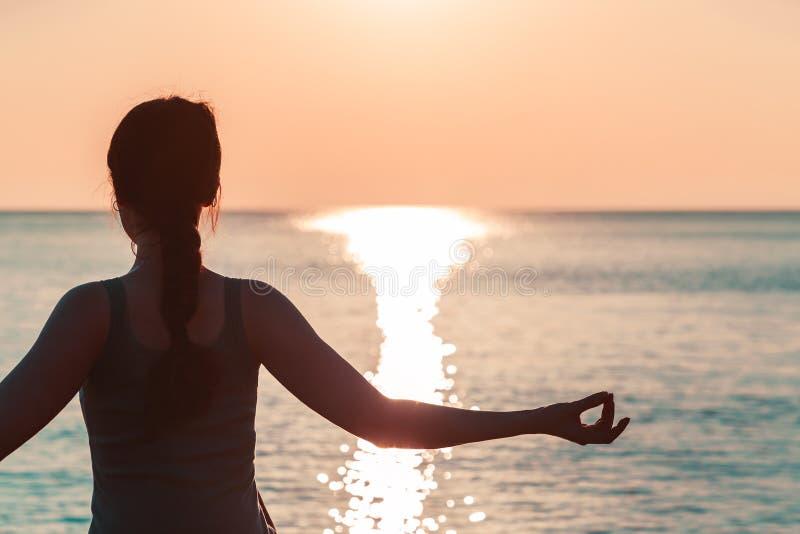 Hand eines Mädchens, das auf dem Hintergrund der Seenahaufnahme meditiert stockfoto