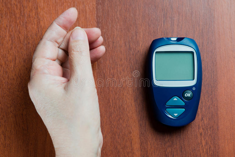 the hand of the elderly woman lies near the device for measurement of level of sugar in blood stock image