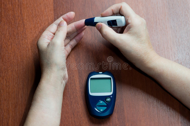 the hand of the elderly woman lies near the device for measurement of level of sugar in blood stock images