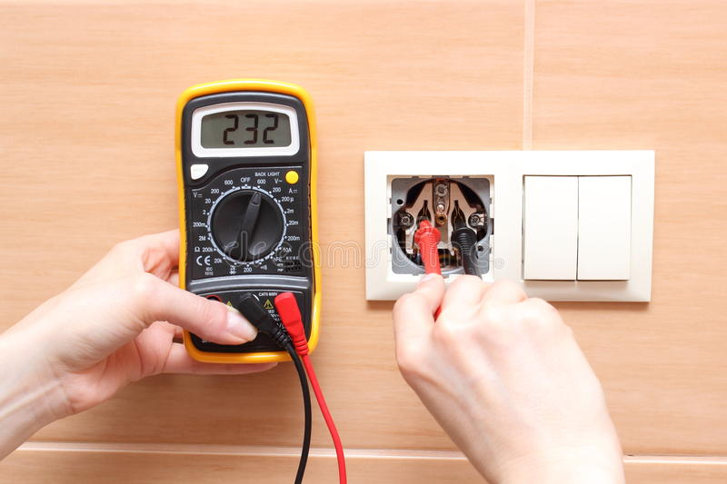 Hand electrician checking voltage. Hand electrician with multimeter checking voltage royalty free stock photos