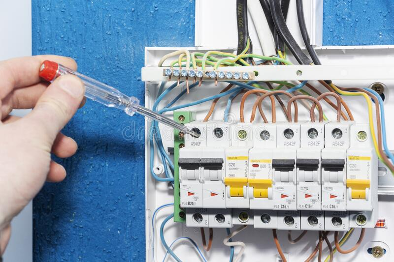 Hand of an electrician with multimeter probe at an electrical switchgear cabinet stock photo