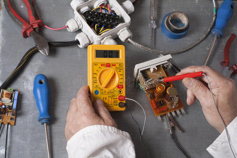 Hand of electrician with multimeter probe at electrical switchgear cabinet. Engineering tools royalty free stock photography