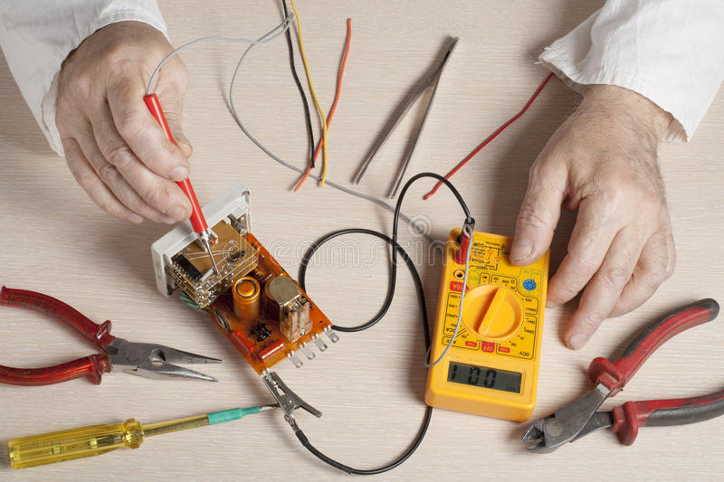 Hand of electrician with multimeter probe at electrical switchgear cabinet. Engineering tools royalty free stock image