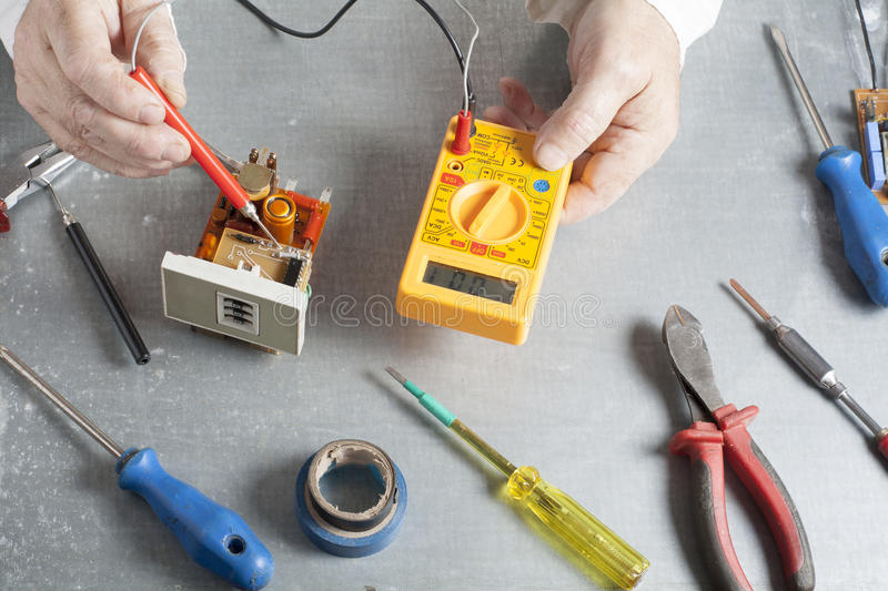 Hand of electrician with multimeter probe at electrical switchgear cabinet. Engineering tools stock image