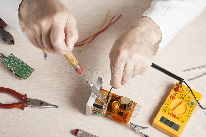 Hand of electrician with multimeter probe at electrical switchgear cabinet. Engineering tools royalty free stock photo