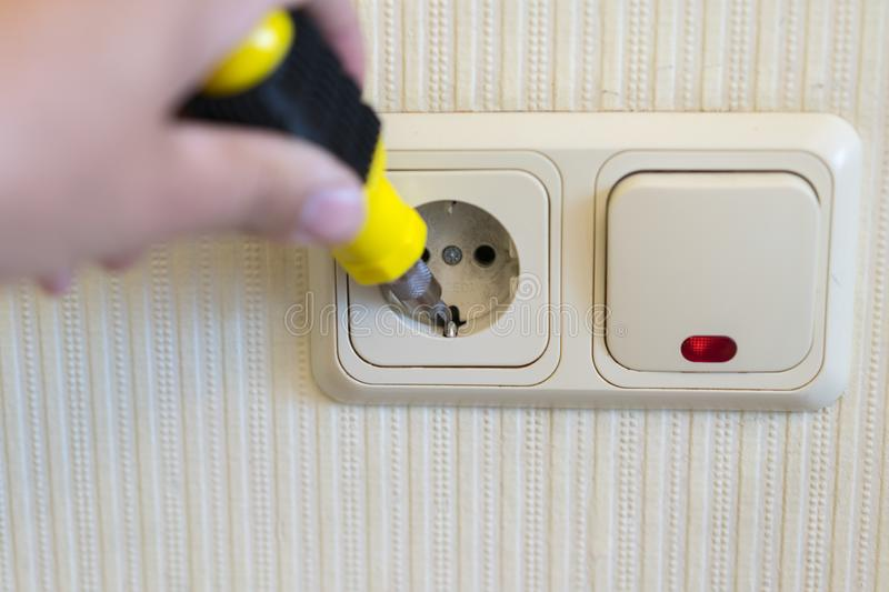 Hand Of An Electrician To Repair A Wall Socket. Closeup of man electrician's hand repairing an electrical outlet. Hazardous stock images
