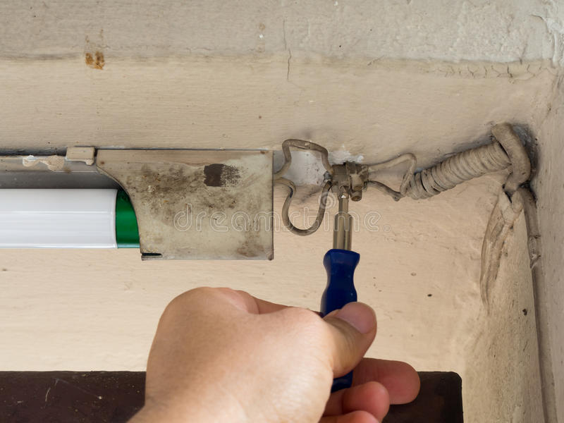 The hand of electricians holds a screwdriver. Rehearsing light system royalty free stock photography