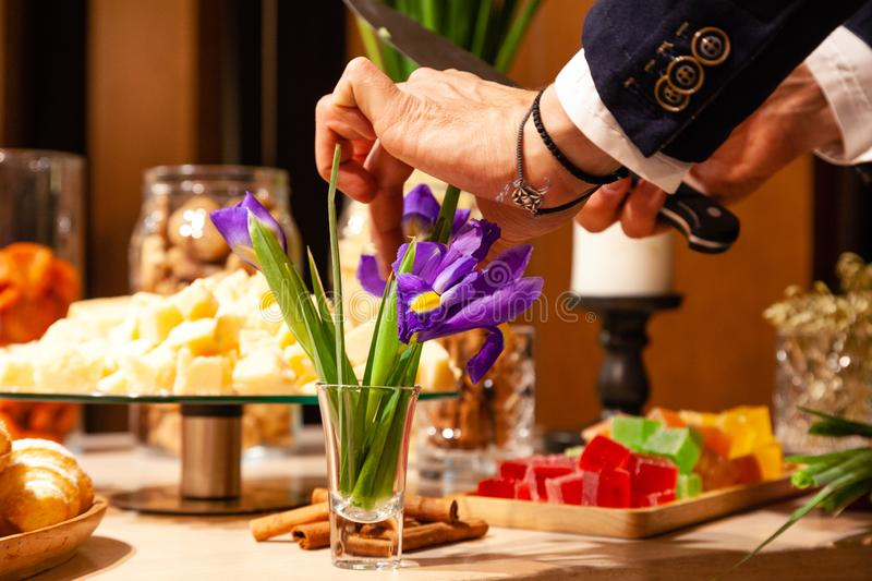 Hand of elegant man with leather bracelet cuts flowers purple irises in glass vase against a buffet table with treats and snacks. stock photography
