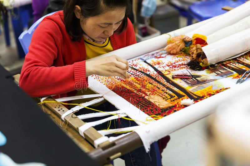 Hand embroidered painting factory in Vietnam. Unidentified woman working in hand embroided painting factory near Halong in Vietnam. These artworks usually stock images
