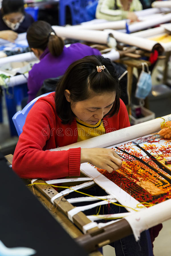 Hand embroidered painting factory in Vietnam. Unidentified women working in hand embroided painting factory near Halong in Vietnam. These artworks usually stock photo