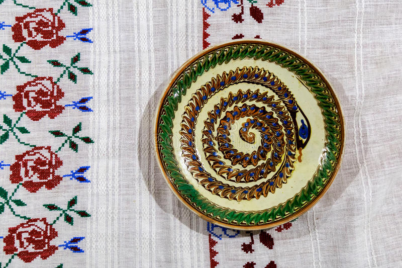 Hand embroidered tablecloth with decorative ceramic plate.Decorative ceramic plate royalty free stock photography
