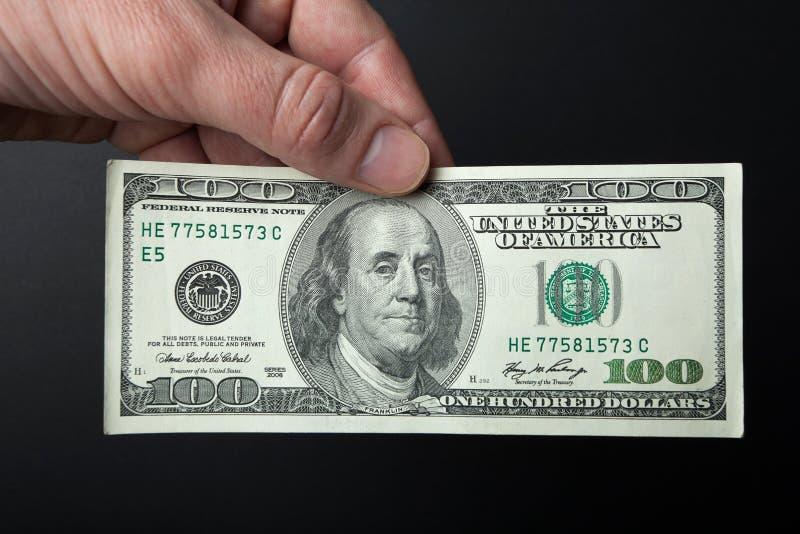 Hand en 100 dollarrekening op een zwarte achtergrond Close-up royalty-vrije stock afbeeldingen