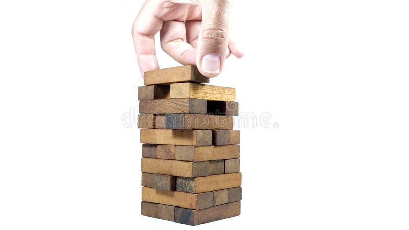 Hand of engineer playing a blocks wood tower game jenga on blueprint or architectural project. Abstract, architecture, brick, build, buildings, choices royalty free stock photography