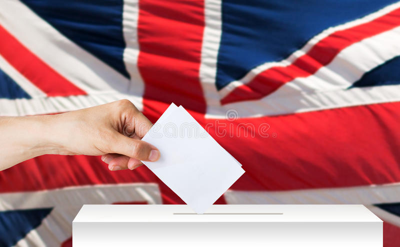 Hand of englishman with ballot and box on election. Voting, civil rights and people concept - male hand putting his vote into ballot box on election over british royalty free stock images