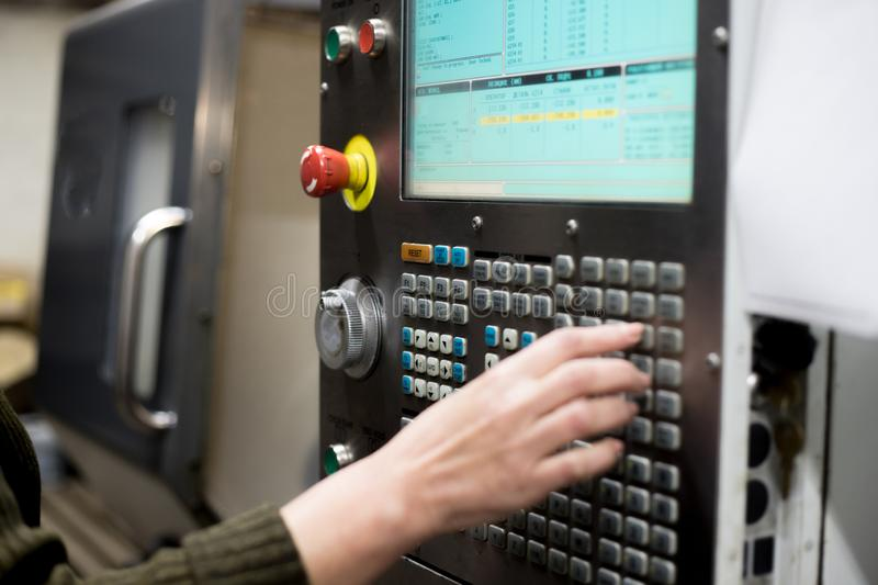The hand enters data on the control panel of the lathe stock images