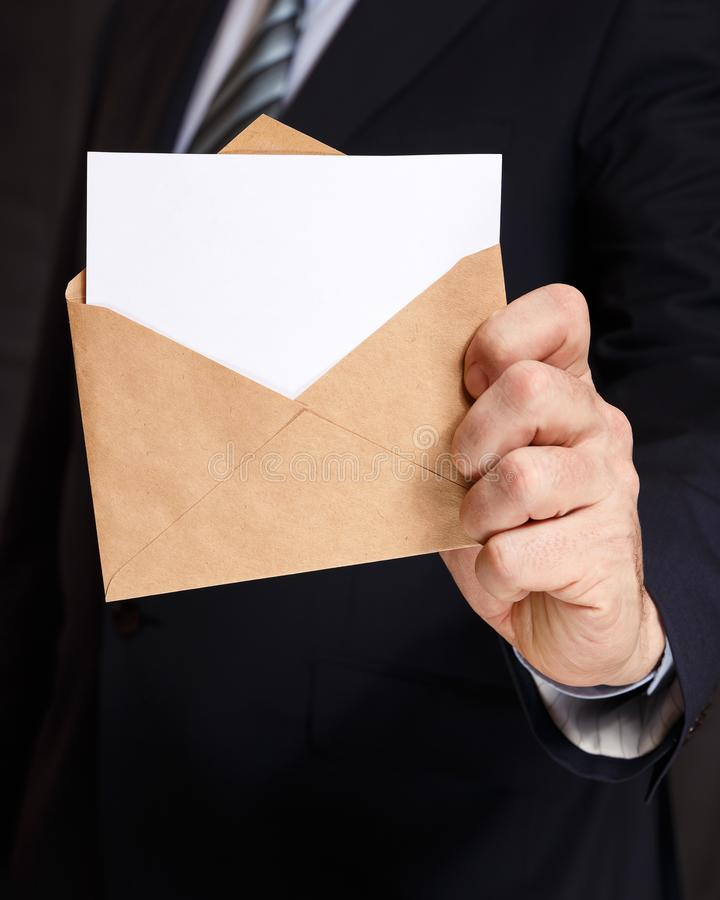 Hand with the envelope and lowered into it with white paper stock images